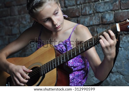 Child playing acoustic guitar in the street - stock photo