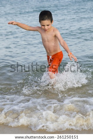 Child playing and running in shallow sea water on a beach in summer. - stock photo
