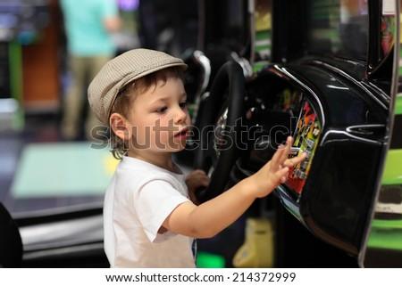 Child playing arcade game machine at an amusement park - stock photo