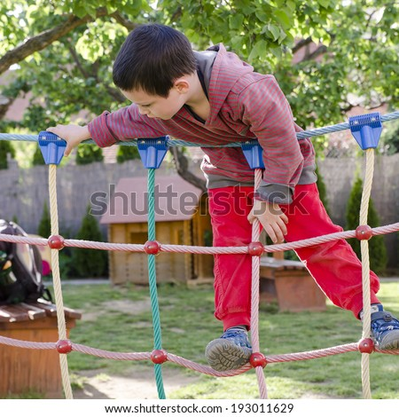 Child playing at children playground, climbing on  rope ladder obstacle course equipment. - stock photo