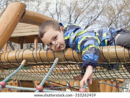 Child playing at children playground, climbing the  rope ladder frame.