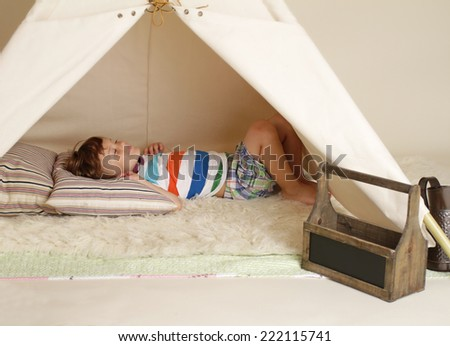 Child playing at home indoors with a teepee tent, taking a nap