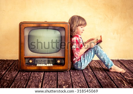 Child playing at home. Kid reading the book near retro TV. Cinema concept - stock photo