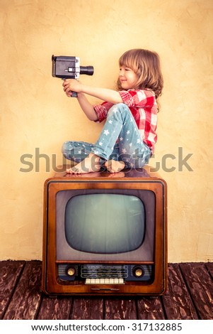 Child playing at home. Kid taking selfie with retro camera. Cinema concept - stock photo