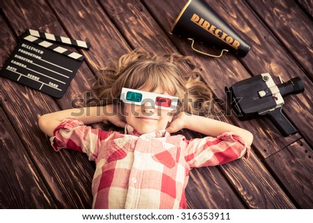 Child playing at home. Kid with vintage cinema objects. Entertainment concept. Top view - stock photo