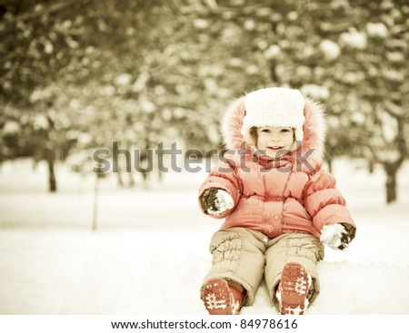 Child playing at snowballs in winter park - stock photo