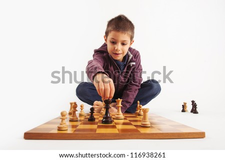 Child playing chess, isolated on white background. - stock photo