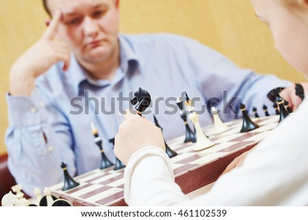 Child playing chess with father