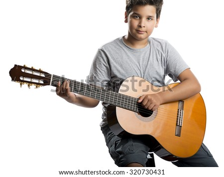 Child playing classical guitar isolated on white background. - stock photo