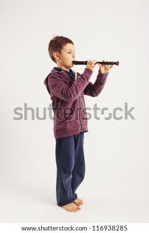 Child playing flute, isolated on white background. - stock photo
