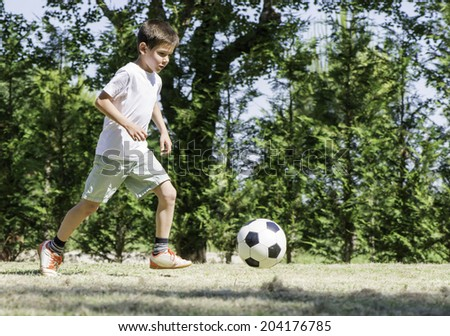 Child playing football in a stadium. Trees on the background - stock photo