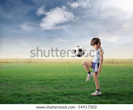 Child playing football on a green meadow - stock photo