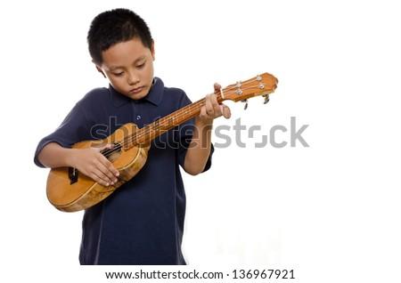child playing his ukulele seriously against the white background - stock photo
