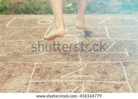 child playing hopscotch on playground outdoors