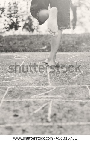 child playing hopscotch on playground outdoors - stock photo