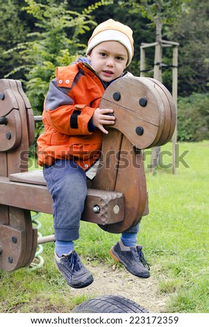 Child playing in a playground in a park swinging on a wooden seesaw. - stock photo