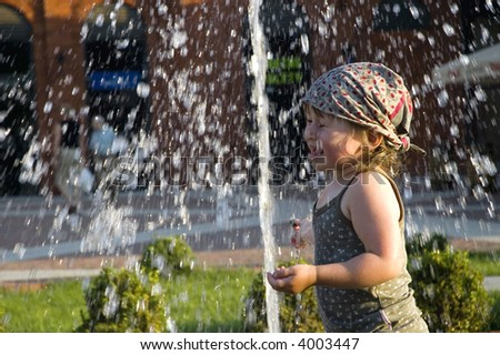 child playing in a public fountain. summer scenic - stock photo
