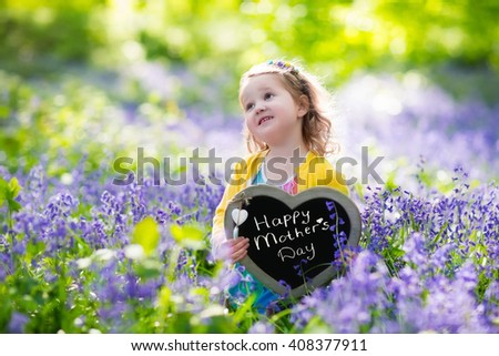 Child playing in bluebells forest. Little girl holding a wooden heart shape chalk board standing in a park with beautiful spring bluebell flowers. Copy space for your text. Happy mother's day card. - stock photo