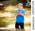 Child playing in mud in forest creek - stock photo