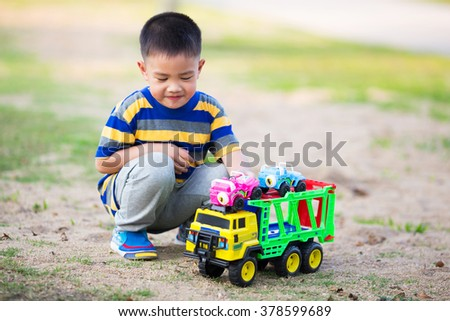 Child playing in sandpit with toy truck car