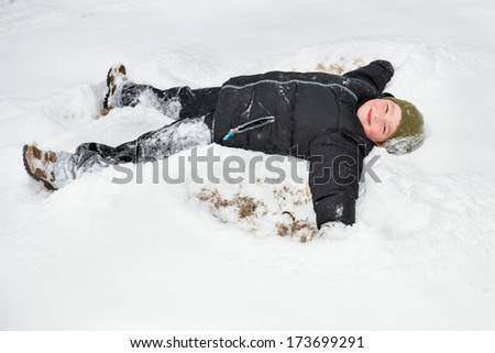 Child playing in snow by making snow angel - stock photo