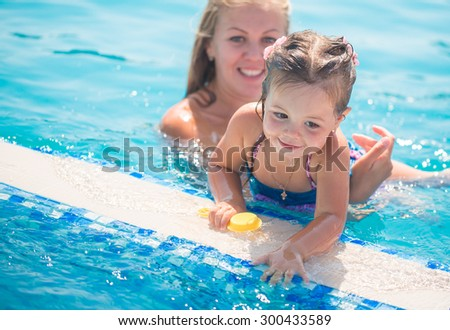 Child playing in swimming pool - stock photo