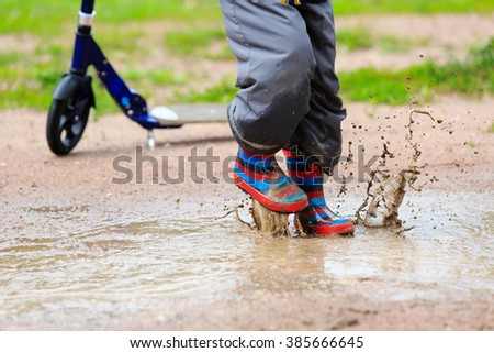 child playing in water puddle, kids outdoor