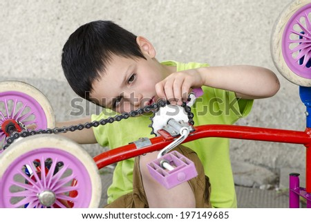 Child playing mechanic  and repairing children tricycle - stock photo