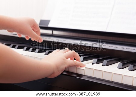 Child playing on a digital piano.