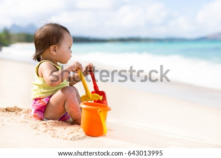 Child playing on sandy beach with a bucket and shovel