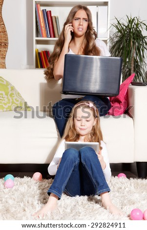 Child playing on tablet while busy mother is working - stock photo