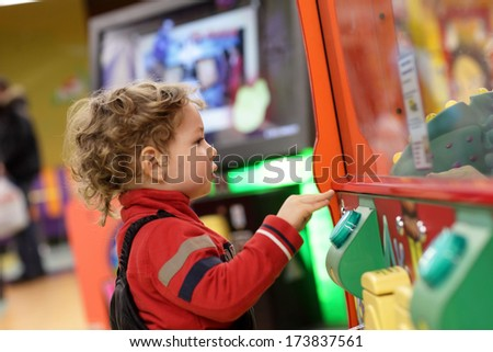 Child playing on the kids game machine at an amusement park