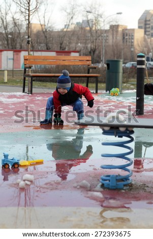 Child playing on the playground in spring - stock photo