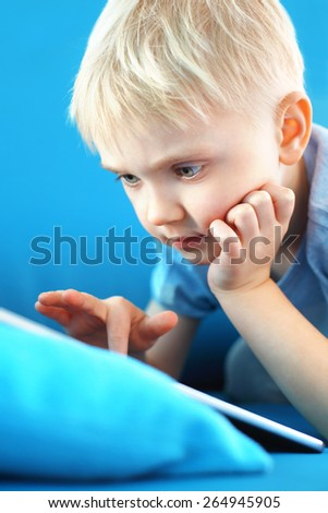 Child playing online games,Little boy, preschooler with a digital tablet on a blue background  - stock photo