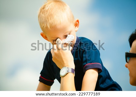 Child playing outdoor and blowing nose in handkerchief. Little boy kid sneezing in tissue. Catarrh or allergy to pollen symptom. - stock photo