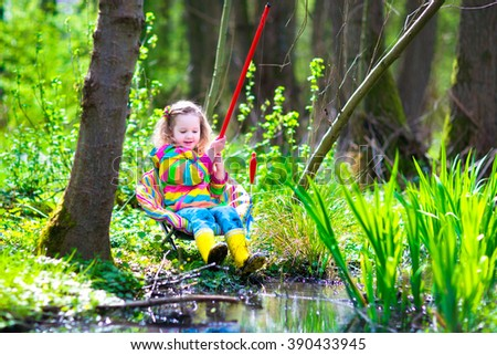 Child playing outdoors. Preschooler kid catching fish with red rod. Little girl fishing in forest river in summer. Adventure kindergarten day trip in wild nature, explorer hiking and watching animals. - stock photo