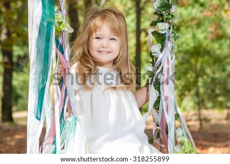 Child, Playing, Playground. Happy little girl on a swing - stock photo