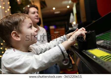 Child playing shooting game at playground - stock photo