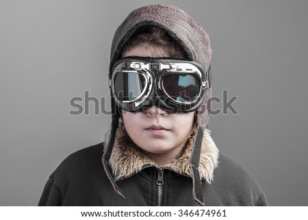 child playing the aircraft pilot with hat and retro bomber jacket