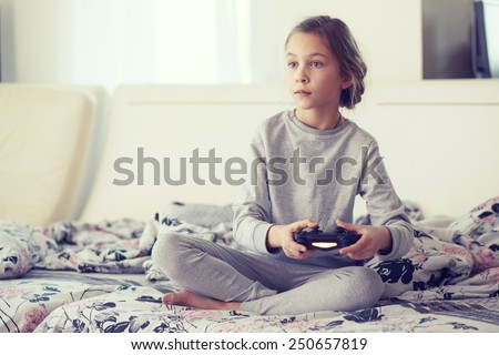 Child playing video game on tv in morning at parent's bedroom at home - stock photo