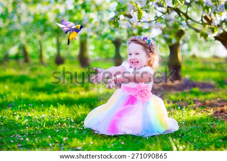 Child playing with a bird. Happy laughing little girl in fairy costume with wings feeding a pet parrot in a cherry tree garden. Kid having fun in blooming fruit orchard in spring. Kids gardening. - stock photo