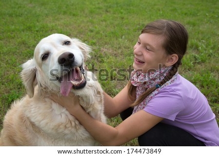 Child playing with a dog on a green meadow