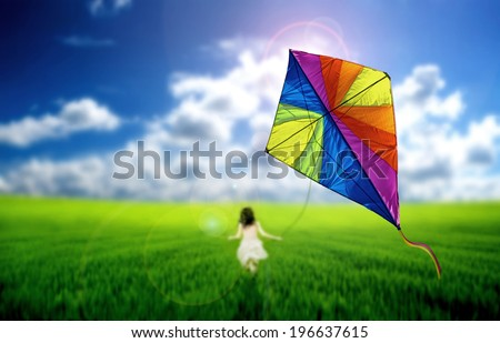 Child playing with a kite on a meadow - stock photo