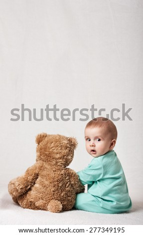 child playing with a plush toy . soft toy. funny baby with a soft toy . layout for social projects - stock photo