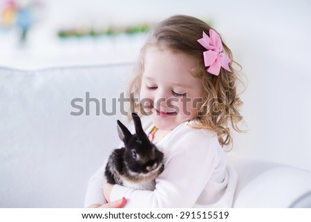 Child playing with a real rabbit. Kids play with pets. Little girl holding bunny. Children and animals at home or preschool. Cute curly toddler kid hugs her pet animal. Preschooler feeding rabbits. - stock photo