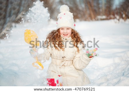 Child playing with a snow enjoying nature on a winter walk in sunny day.