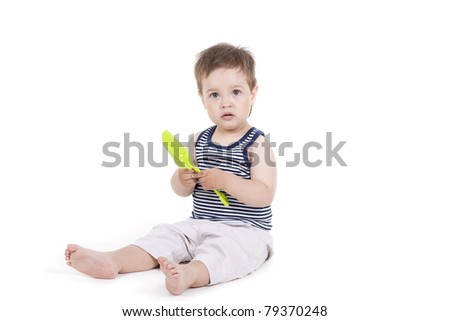 child playing  with a toy shovel on a white background