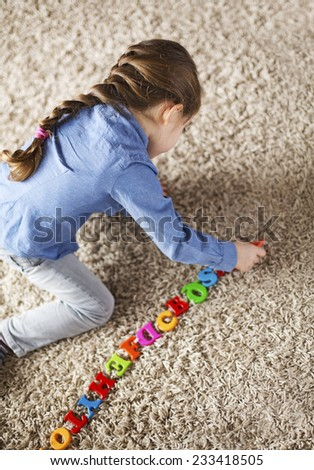 Child playing with alphabet letters at home - stock photo