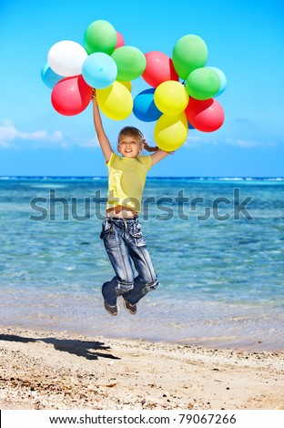 Child playing with balloons at the beach.