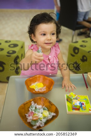 Child playing with candy and puzzle toys - stock photo